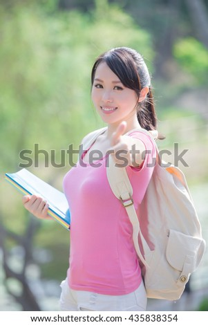 young woman student smile to you and show thumb up gesture. nature green background - stock photo