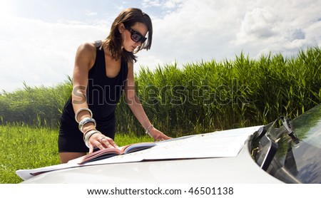 Young woman, studying a map and a guide book on the hood of her car on a bright summer day - stock photo