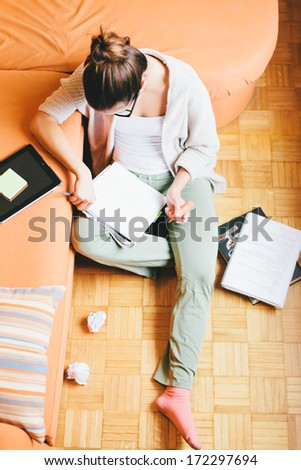 Young woman studying in living room - stock photo