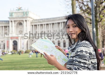 Young woman studying map near the national Library in center Vienna, Austria  - stock photo