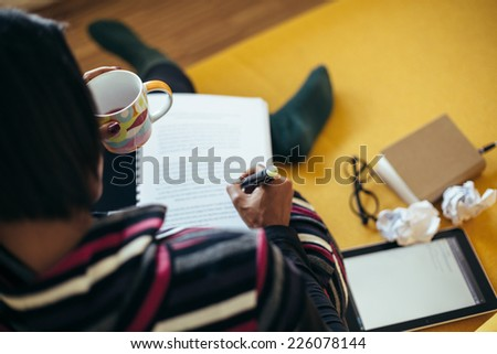 Young woman studying on the couch - stock photo