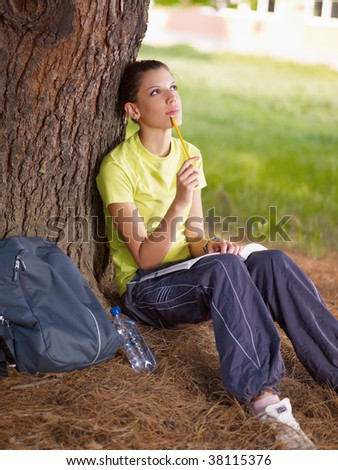 young woman studying outdoors and leaning on tree