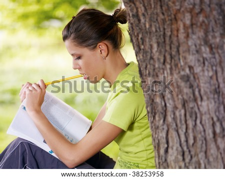 young woman studying outdoors and leaning on tree. Copy space - stock photo