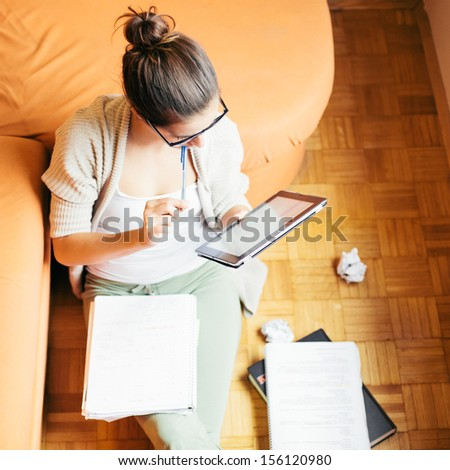 Young woman studying sitting on the floor - stock photo