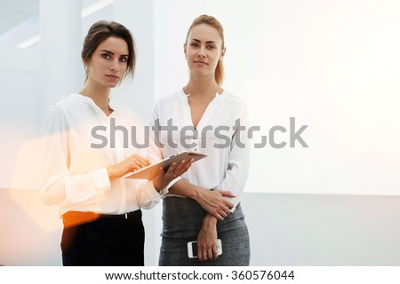 Young woman successful manager holding digital tablet while standing with her female partner in modern office interior, confident smart businesswomen using touch pad while preparing to the meeting  - stock photo