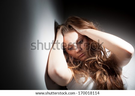 Young woman suffering from a severe depression, anxiety (very harsh lighting is used on this shot to underline the gloomy mood of the scene, color toned image) - stock photo