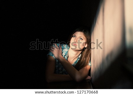 Young woman suffering from a severe depression in a line of light - stock photo