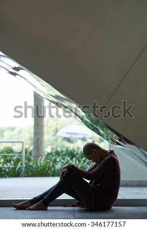 Young woman suffering from cancer sitting under the staircase