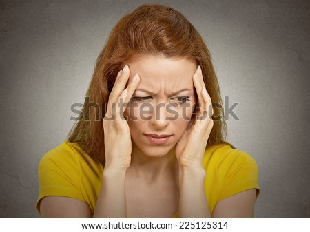 Young woman suffering from headache hands on head temples isolated on grey wall background. Human face expression emotion feeling