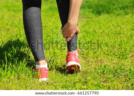 Young woman suffering from pain in leg outdoors