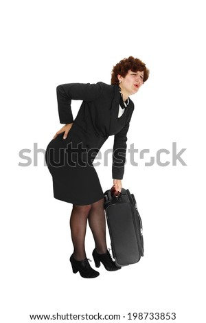 Young woman suffers from back pain lifting a heavy suitcase isolated on white background