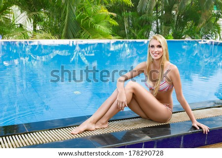Young woman sun bathing in tropical spa resort swiming pool - stock photo