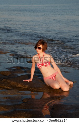Young woman sunbathing at the seaside in the morning - stock photo