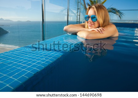 young woman sunbathing by the pool on the roof of the penthouse in Rio de Janeiro on Copacabana beach background - stock photo