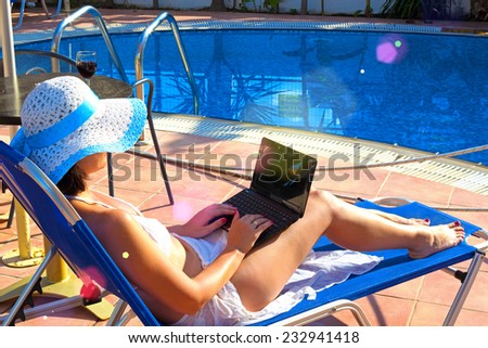 Young Woman sunbathing on deckchair with laptop ; Young woman relaxes by the pool with a laptop - stock photo
