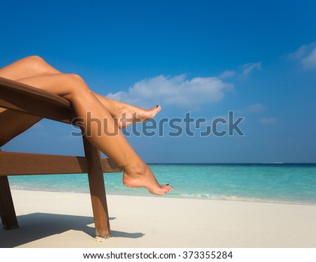 Young woman sunbathing on lounger. Legs. - stock photo