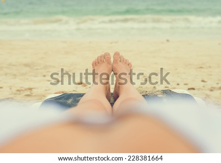 Young woman sunbathing on lounger. Legs. Vintage effect. - stock photo