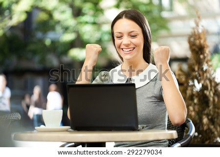 Young woman surfing the net on laptop in a cafe