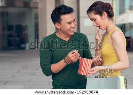 Young woman surprised by a gift of her boyfriend - stock photo