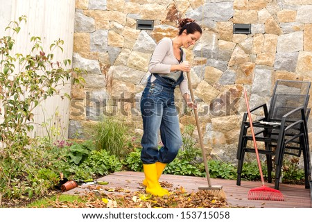 Young woman sweeping autumn leaves veranda backyard cleaning pile - stock photo