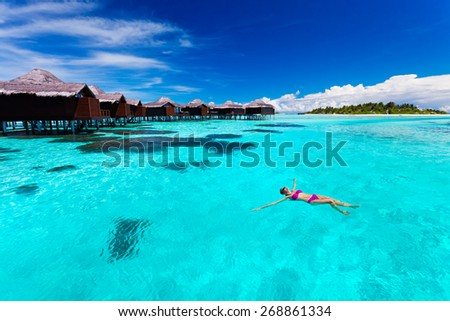Young woman swimming from hut in blue tropical lagoon - stock photo