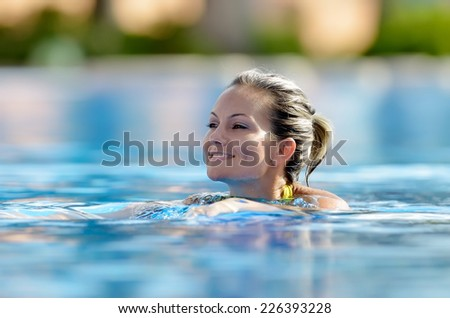 young woman swimming in the pool on a warm summer day - stock photo