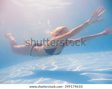 Young woman swimming underwater in the swimming pool - stock photo