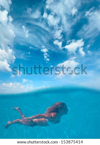 Young woman swimming undewater  - stock photo