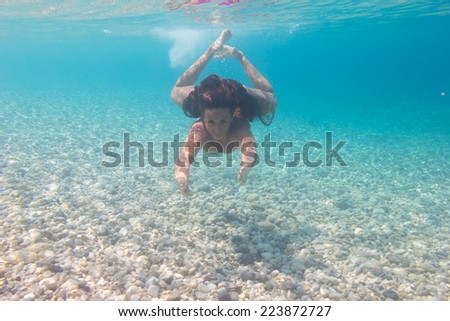 Young woman swimming undewater in the sea
