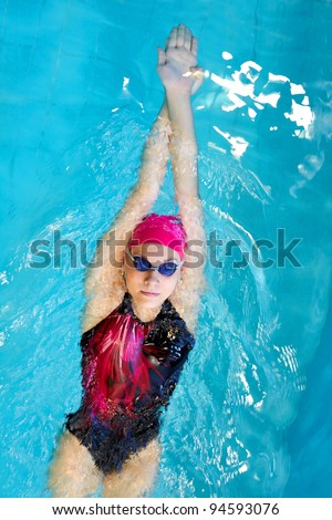young woman swims on back in the pool - stock photo