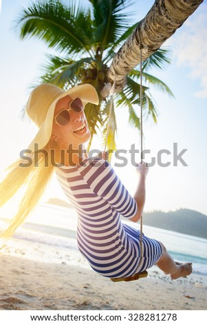 Young woman swinging at tropical beach smiling into the camera - stock photo