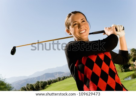 Young woman swinging club on golf course