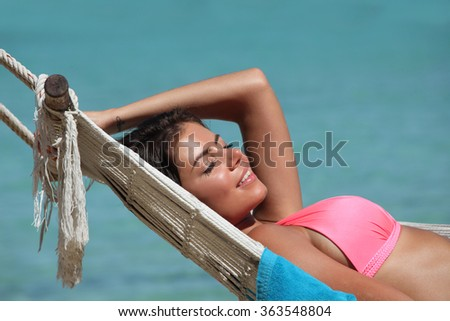 Young woman swinging in hummock on blue sea background - stock photo