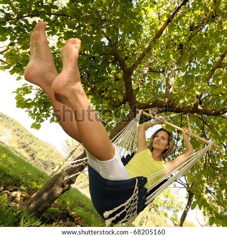 young woman swinging outdoor in summer