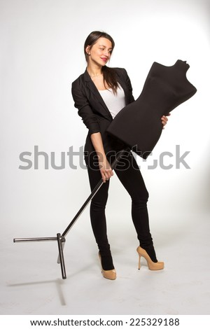 Young Woman tailor holding on Mannequin - stock photo