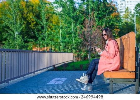 Young woman take a photo by her phone at autumn day - stock photo