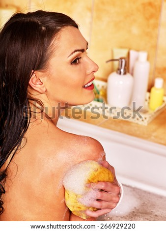 Young woman take bubble  bath. Woman washing her shoulder. - stock photo