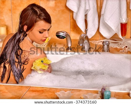 Young woman take bubble  bath. Woman washing her shoulder by yellow sponge. - stock photo
