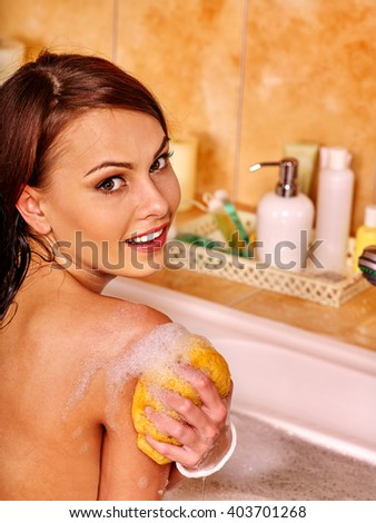 Young woman take bubble  bath. Woman washing her shoulder. She is happy. - stock photo