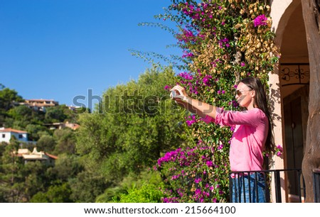 Young woman take photo on her phone at tropical beach - stock photo