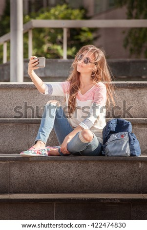 young woman take selfie with wind in hair day shot in the city - stock photo
