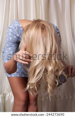 Young woman takes care of the hair, combing their - stock photo