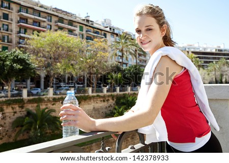 Young woman taking a break from exercising in the city, holding a blue plastic bottle of mineral water and with a white towel over her shoulder during a sunny morning.
