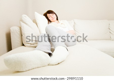 Young woman taking a nap on a couch - stock photo