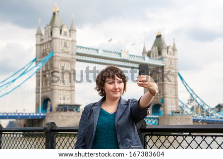 Young woman taking a photo of herself in front of the Tower Bridge. London, England - stock photo