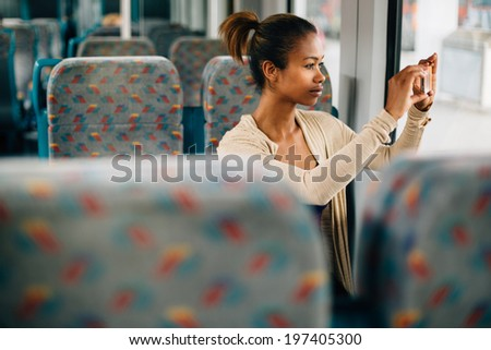 Young woman taking a photo on train with her phone - stock photo