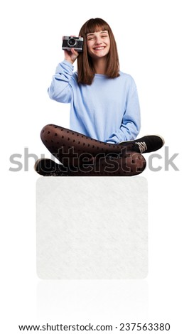 young woman taking a photo sitting on a box isolated on white - stock photo