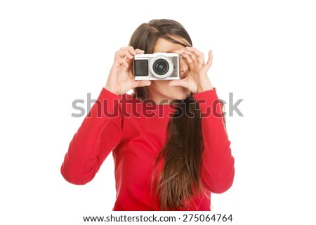 Young woman taking a photo with a camera. - stock photo