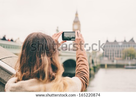 Young woman taking a photo with her phone in London - stock photo