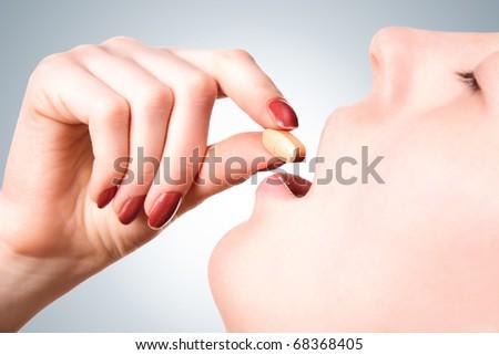 Young woman taking a pill closeup. - stock photo